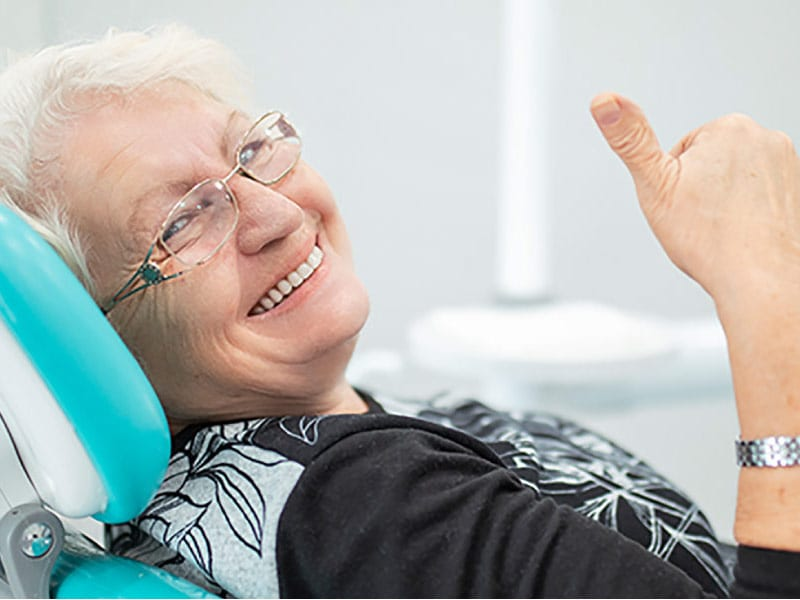 senior woman gives a thumbs up in the dental chair after getting fitted with dentures