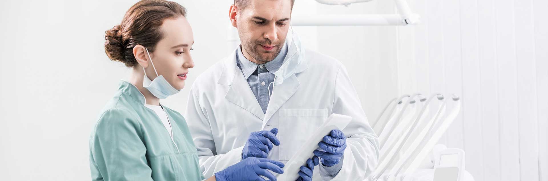 Dentists standing and looking at digital tablet in dental clinic