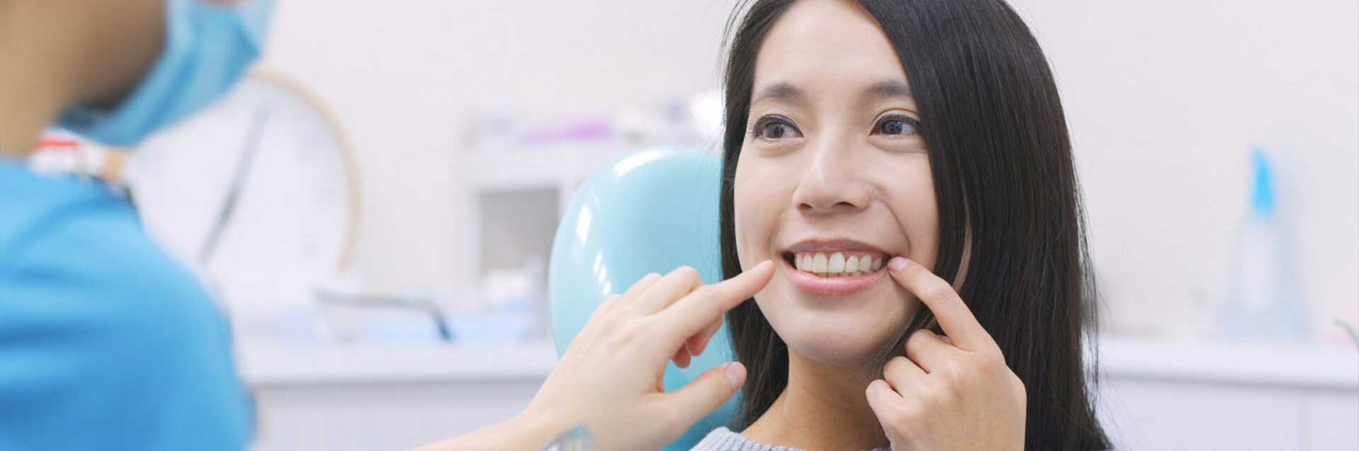 Woman pointing at her teeth to show dental implants