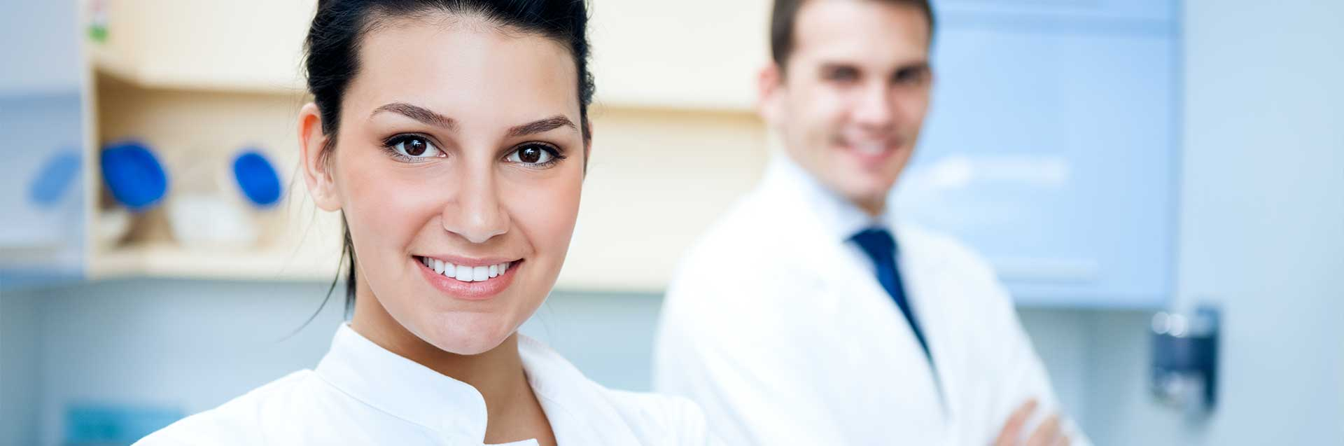 A female dentist and a male smiling while looking at the camera at their dental office